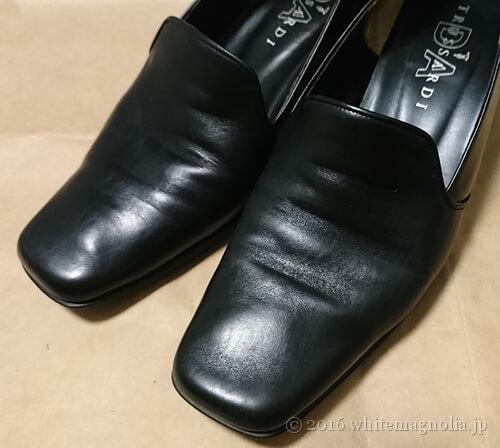 黒パンプスに塗った靴墨の余計な分を布で拭いた後